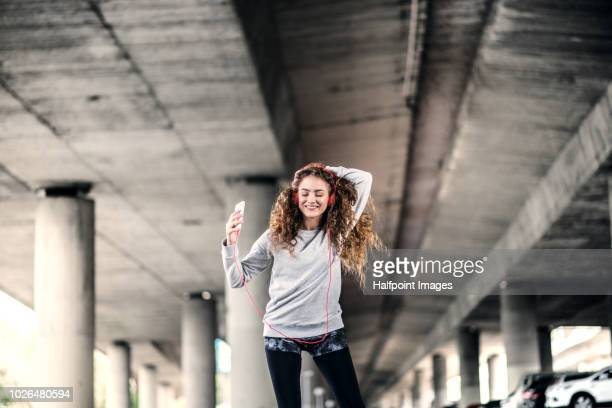 a beautiful young woman with smartphone and red headphones under the bridge in the city, listening to music. - practicing stock photos and pictures