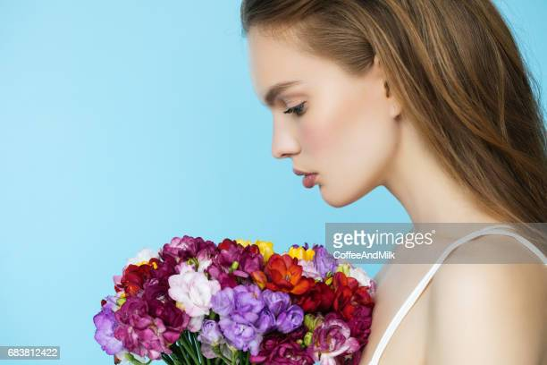 Beautiful young woman with spring bouquet