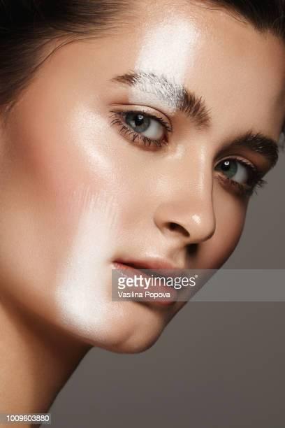 beautiful young woman with white strip make-up - junge frau allein stock-fotos und bilder