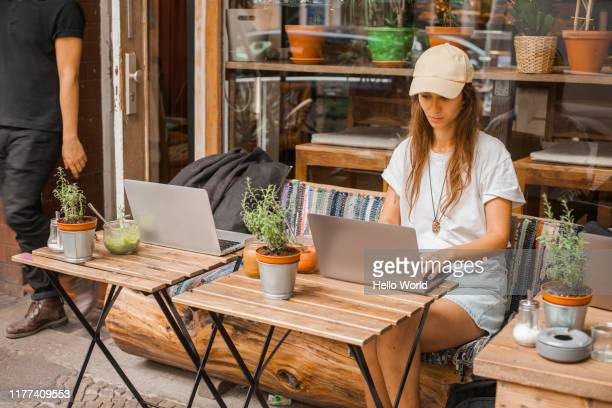 beautiful young woman woking on the go outside a street cafe - good posture stock pictures, royalty-free photos & images