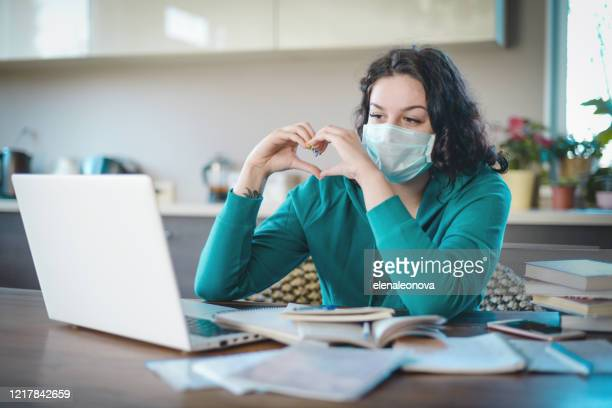 beautiful young woman working at home in the mask ( video conference) - romance stock pictures, royalty-free photos & images