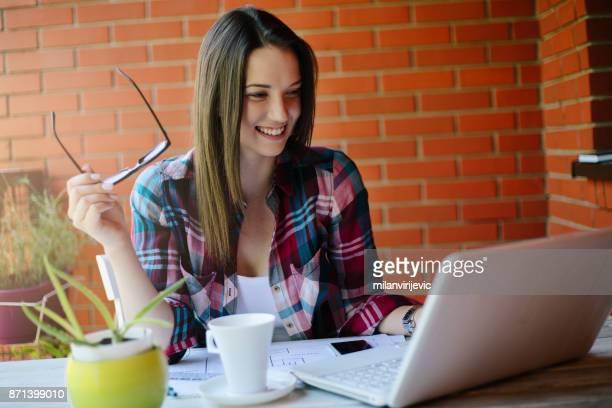 Schöne junge Frau, die Arbeiten an der Terrasse