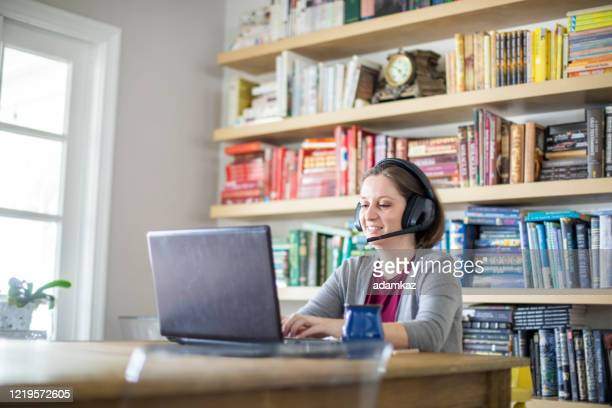 beautiful young woman working from home - adamkaz stock pictures, royalty-free photos & images