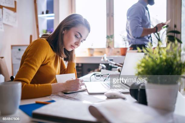 Beautiful young woman working in office with her colleague