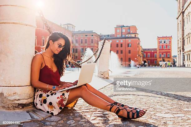 beautiful young woman working on her laptop outdoors