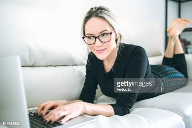 Schöne junge Frau, die mit laptop