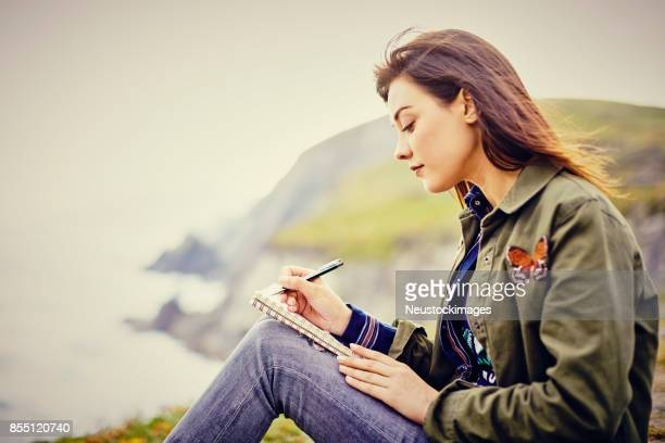 beautiful young woman writing in diary while sitting on mountain - diary stock pictures, royalty-free photos & images