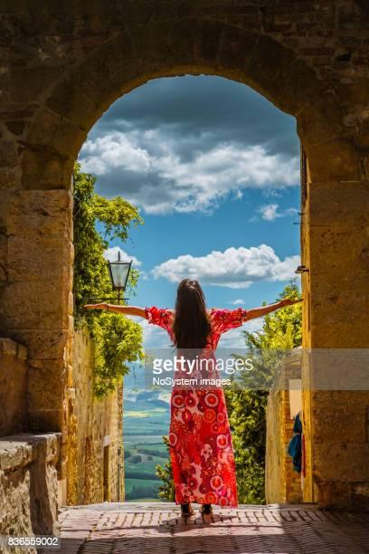 赤いドレスの美しい若い女性は、古い町ピエンツァでお楽しみください.
