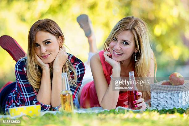 Beautiful young women in the park laying on the grass