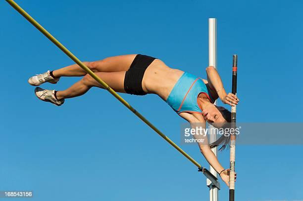 Schöne junge Frau springt über den lath