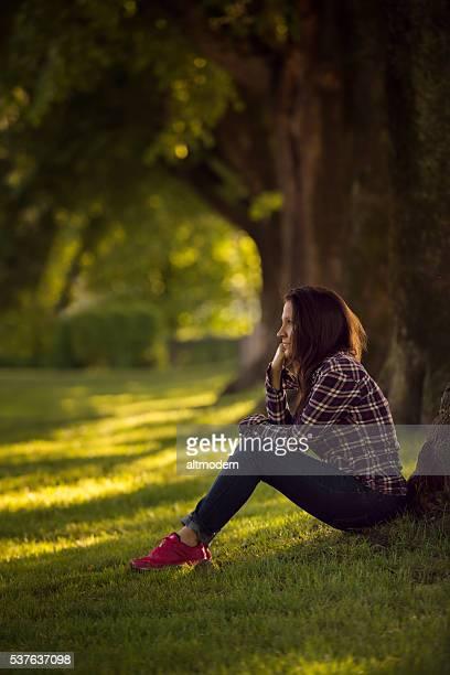 beautiful young women sitting in a park - attraktive frau stockfoto's en -beelden