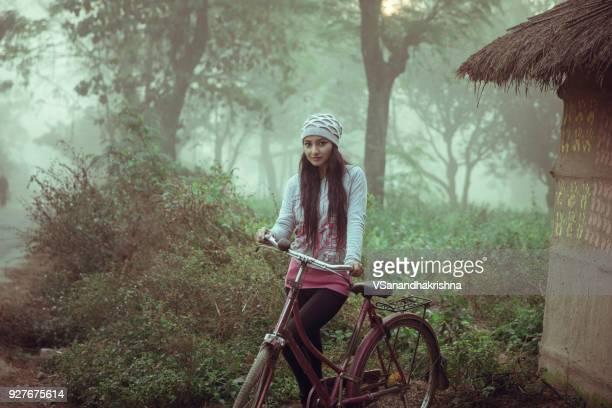 自転車の側に立って美しい若い女性