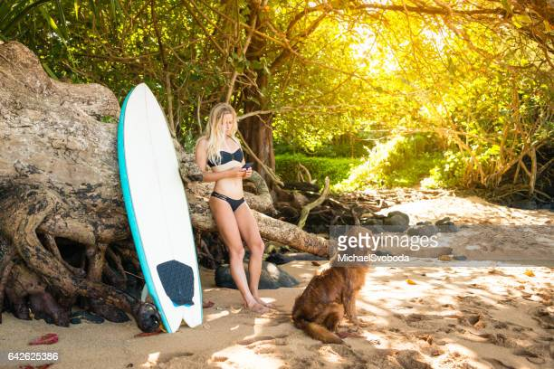 Beautiful Young Women Surfer And Her Dog Texting