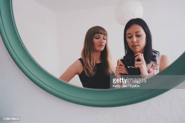 beautiful young women taking photo in mirror - mirror selfie stock pictures, royalty-free photos & images