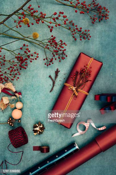 beautifully wrapped christmas present surrounded by various christmas decorative items, a flat lay - branch stock pictures, royalty-free photos & images
