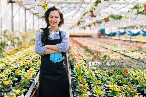 Beautuful young gardener in a greenhouse