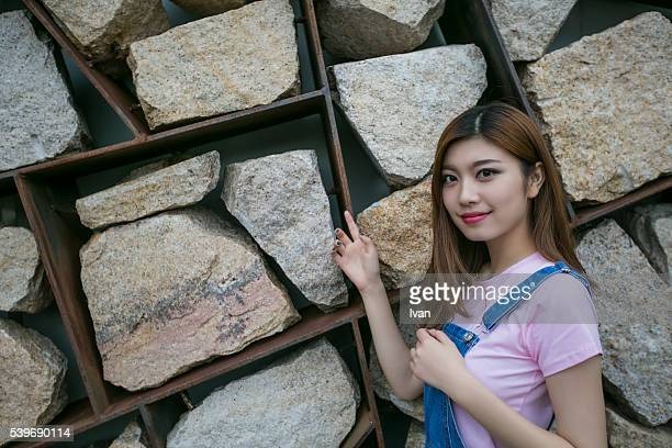 A Beauty Asian Young Woman Against Stone Wall