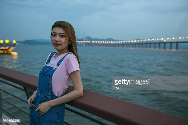 A Beauty Asian Young Woman Looking at Camera on a Bridge Against Sea at Night