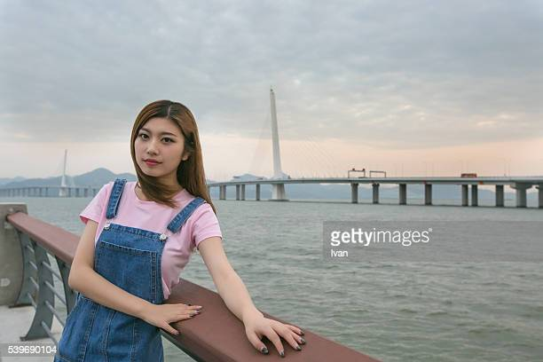 A Beauty Asian Young Woman Looking at Camera on a Bridge Against Sky and Sea