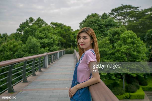 A Beauty Asian Young Woman Looking at Camera on a Stone Bridge Against Armrest and Blue Sky and Forest