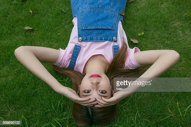 A Beauty Asian Young Woman Lying down on a Grass Field and Looking at Camera