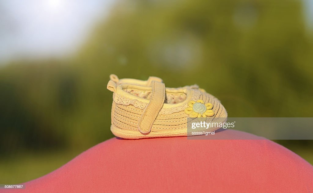 Beauty baby shoes on the mother's belly : Stock Photo