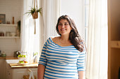Beauty, bodypositivity, people and lifestyle concept. Indoor shot of gorgeous brunette Latin girl posing by window in kitchen dressed in xxl blue and white striped shirt, having joyful beaming smile