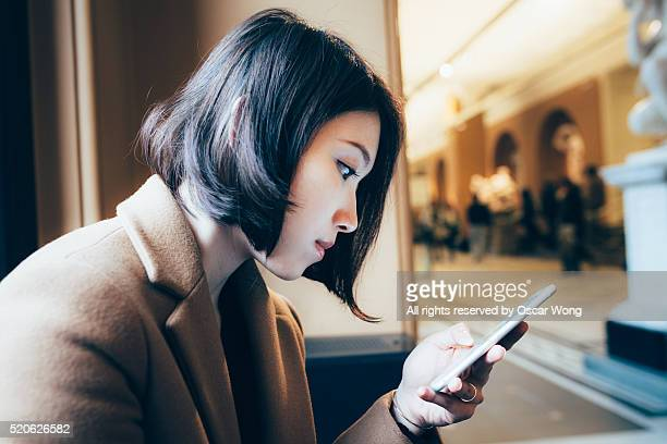 Beauty business woman using smartphone in lobby