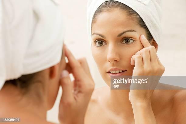 Belleza revisando su piel en el espejo buscando arrugas (XXXL