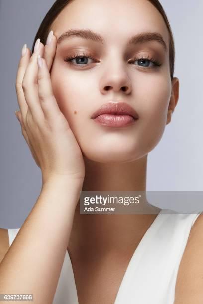 beauty cosmetic shot of a beautiful young woman touching her face