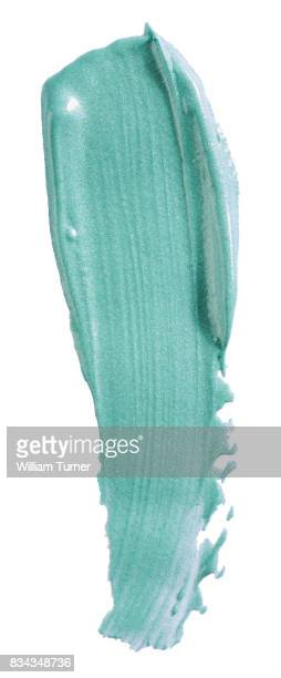 A beauty cut out image of a smear, line or swipe sample of pale turquoise or green lip gloss