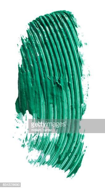A beauty cut out image of a swipe, smear or scrape of green mascara