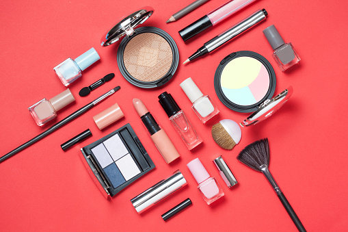 Beauty, decorative cosmetics. Makeup brushes set and color eyeshadow palette on pink and blue background , flat lay, top view, Minimalistic style. red background 930934354
