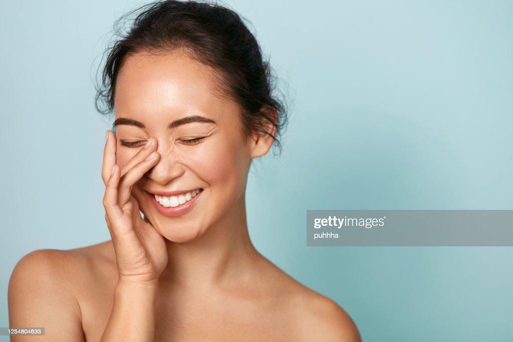 Schoonheidsgezicht. Glimlachende Aziatische vrouw die gezond huidportret raakt : Stockfoto