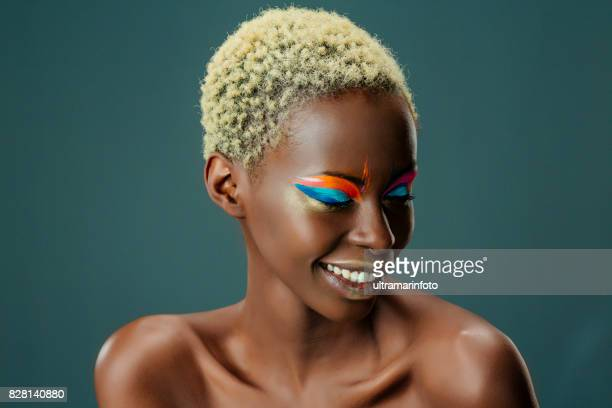 beauty, fashion portrait. original looks. beautiful, lovely and sensual young african girl. attractive african ethnicity, slim women, blonde, short hair. gray wall background. - stage make up stock photos and pictures