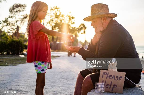 beauty girl giving money to homeless men - homeless person stock pictures, royalty-free photos & images