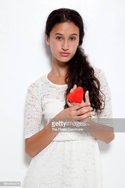 Beauty girl with red heart against chest in studio