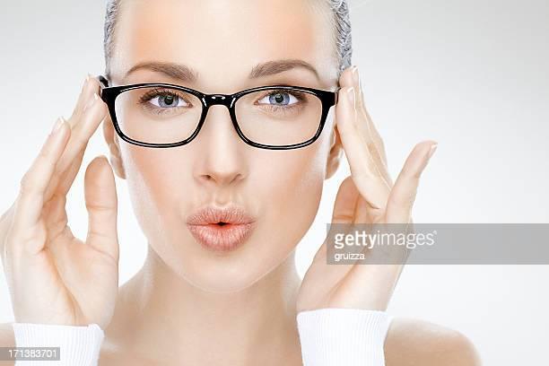 Beauty Portrait der schönen Frau hält eyeglasses und Blasen-Küsse