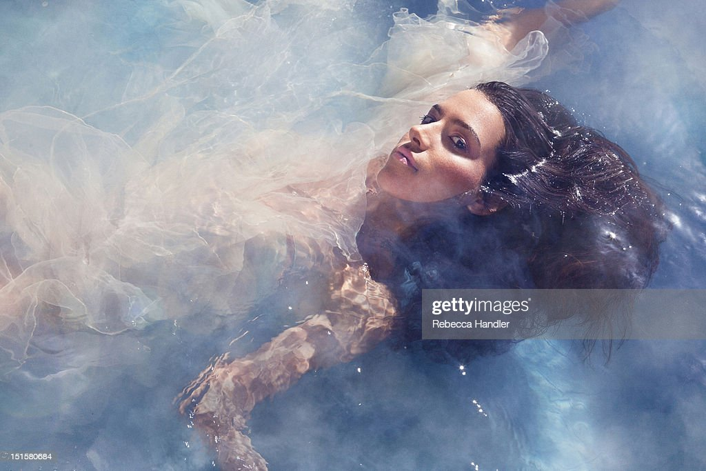 Beauty image of woman in water with smoke : Stock Photo