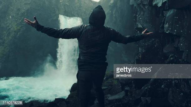 beauty in nature. traveler admiring waterfall. open arms - the four elements stock pictures, royalty-free photos & images