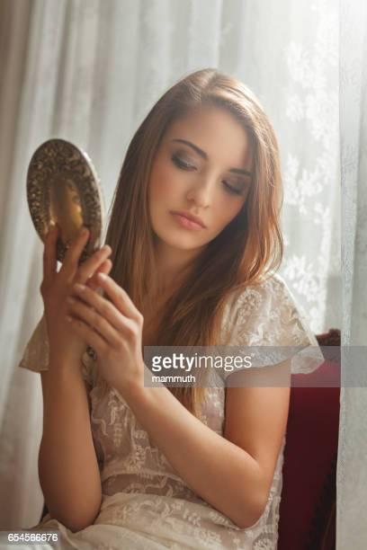 Belleza a sí misma mirando en un espejo de mano