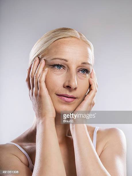 beauty mature woman tightening a face with her hands. - tighten stock photos and pictures