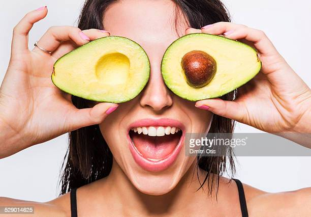 Beauty model holding avocado halves over her eyes