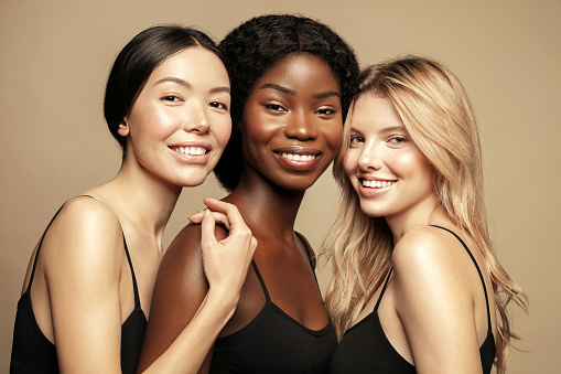 Beauty. Multi Ethnic Group of Womans with diffrent types of skin  together and looking on camera. Diverse ethnicity women - Caucasian, African and Asian posing and smiling against beige background. 1193184392