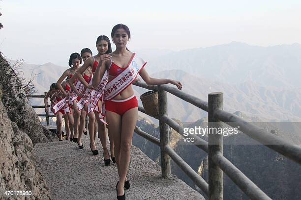 Beauty pageant models in bikinis walk on a cliff pathway 2000 meters above the ground as part of a challenge on April 17 2015 in Luoyang Henan...