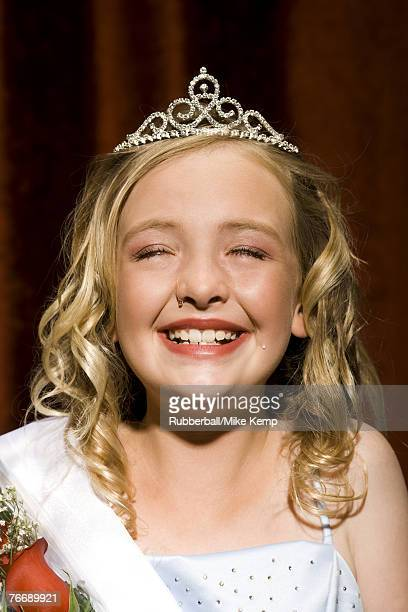 Beauty pageant winner smiling and holding roses