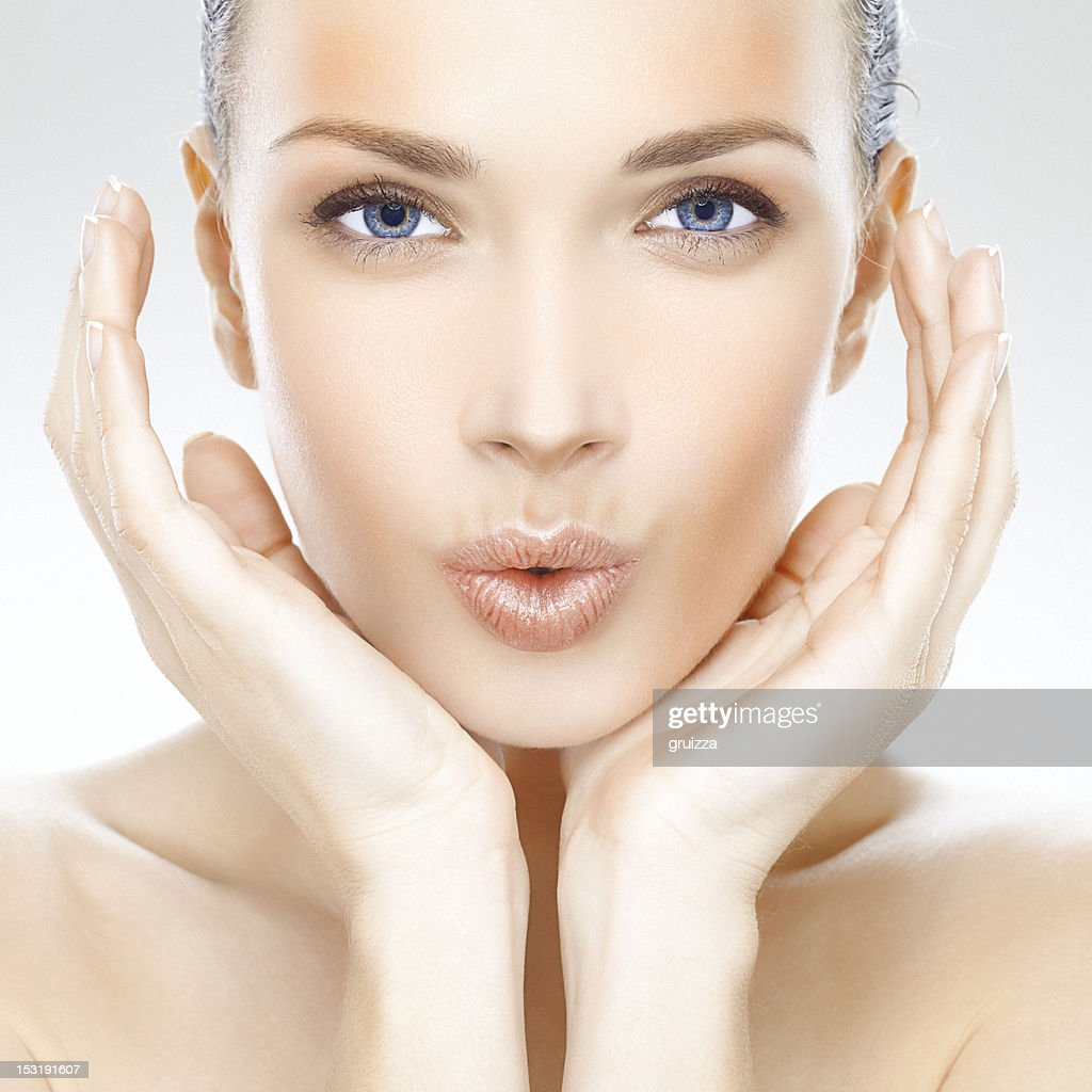 Beauty portrait of a beautiful young woman blowing kisses : Stock Photo