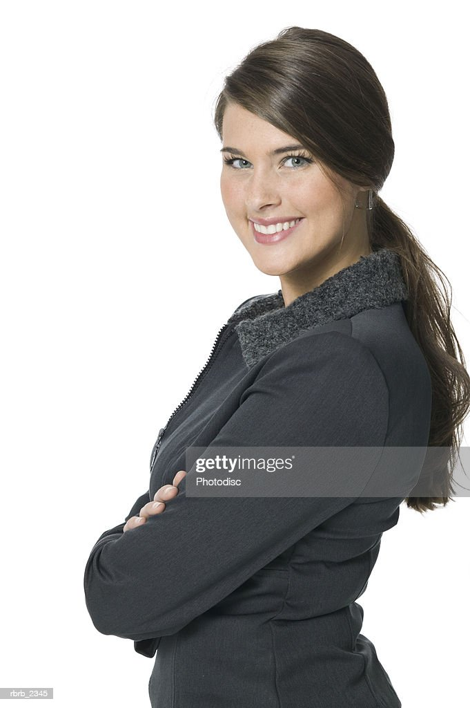 beauty portrait of a brunette young adult woman in a grey outfit as she turns and smiles : Foto de stock