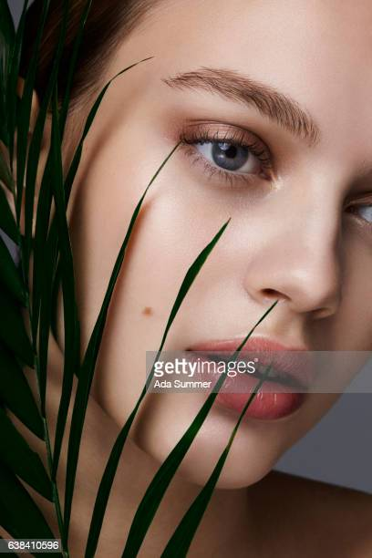 beauty portrait of a woman with palm leaf