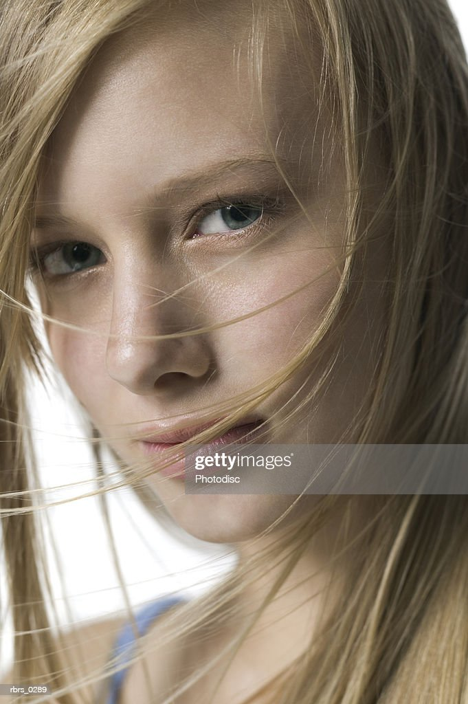 beauty portrait of a young adult blonde girl with wind tossed hair as she glances at the camera : Foto de stock